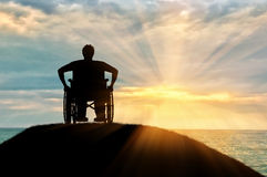 Silhouette of disabled person in a wheelchair. Concept of disability and old age. Silhouette of disabled person in a wheelchair on a hill against a sunset sea Stock Image