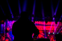 Silhouette of DJ performing in front of a stage stock photo