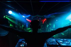 Silhouette of DJ waving his hands in different directions at merry party in night club music event Stock Photography