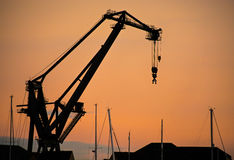 Silhouette dockside crane at sunset. A dockside crane, silhouetted against the setting sun Royalty Free Stock Photo