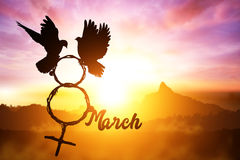 Silhouette of dove holding branch in 8th March text and Venus symbol shape flying on sunset sky Royalty Free Stock Photos
