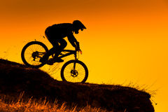 Silhouette of downhill mountain bike rider at sunset. Silhouette of downhill mountain bike rider at orange sunset Royalty Free Stock Photo