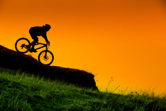 Silhouette of downhill mountain bike rider at sunset. Silhouette of downhill mountain bike rider at orange sunset Stock Photography