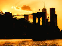 Silhouette of the downtown Manhattan skyline and the Brooklyn Bridge at sunset Royalty Free Stock Photo