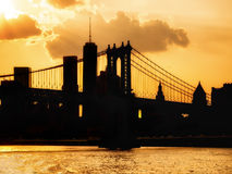 Silhouette of the downtown Manhattan skyline and the Manhattan Bridge at sunset Stock Photos