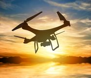 Silhouette of a drone with digital camera flying in a sunset sky Stock Photos