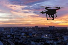Silhouette of drone flying. Above city at sunset royalty free stock photo