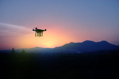 Silhouette of drone flying to the mountain view at sunset Royalty Free Stock Photos