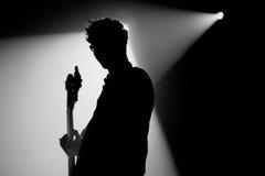 Silhouette du bassiste de nous sommes standard (bande) exécute au clinquant de discothèque Image libre de droits
