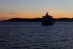 Silhouette du bateau de mer contre un coucher du soleil images stock