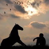 Silhouette du cheval et de l'homme s'asseyant sur l'herbe extérieure Images libres de droits