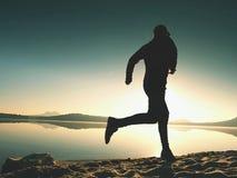 Silhouette du coureur actif d'athlète fonctionnant sur le rivage de lever de soleil Exercice sain de mode de vie de matin Photos stock
