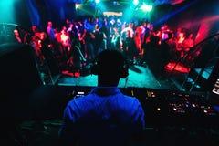 Silhouette du DJ jouant la musique sur le mélangeur et beaucoup de personnes dansant dans la boîte de nuit sur l'étape Photos libres de droits