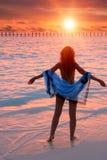 Silhouette du femme contre un coucher du soleil à l'océan image stock