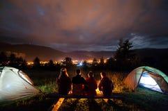 Silhouette du feu d'observation de quatre personnes ensemble dans le camping Image stock