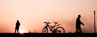 Silhouette du fonctionnement de l'homme et de femme, faisant du vélo et marchant sur le passage couvert à la rive dans la soirée  Photo libre de droits