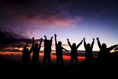 Silhouette du groupe d'amis se tenant dans le coucher du soleil Photographie stock