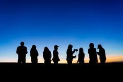 Silhouette du groupe de personnes dans le lever de soleil Photos stock