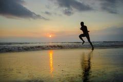 Silhouette du jeune ajustement attrayant sportif et de l'homme afro-américain noir fort courant à la formation de plage de couche photos libres de droits