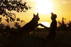 Silhouette du jeune homme et du chien appréciant le beau paysage, garçon avec un ami quadrupède au coucher du soleil dans un doma photographie stock libre de droits