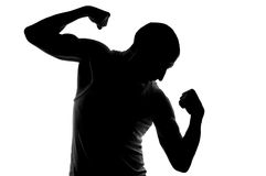Silhouette du jeune homme fort regardant sur son biceps. Photos libres de droits