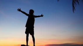 Silhouette du jeune homme réussi soulevant des mains au-dessus de la mer pendant le coucher du soleil stupéfiant Mouvement lent 1 banque de vidéos
