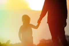 Silhouette du père et de la fille tenant des mains au coucher du soleil Photo stock