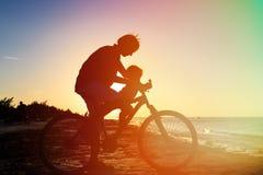 Silhouette du père et du bébé faisant du vélo au coucher du soleil Photos libres de droits