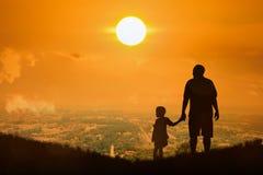 Silhouette du père et du fils se tenant sur la ville Images libres de droits
