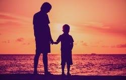 Silhouette du père et du fils tenant des mains à la mer de coucher du soleil images libres de droits