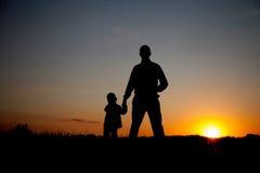 Silhouette du père et du fils tenant des mains au coucher du soleil Photographie stock