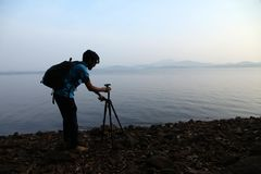 Silhouette du photographe avec le trépied Jeune homme prenant la photo avec son appareil-photo pendant le matin près du lac dans  photographie stock libre de droits