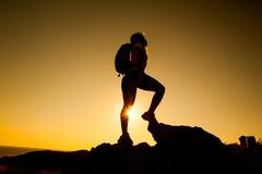 Silhouette du randonneur sur le coucher du soleil Image stock