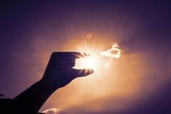 Silhouette du soleil de cueillette de main au ciel bleu et au nuage, fil de vintage Photographie stock libre de droits
