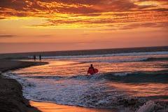 Silhouette du surfer avec la planche de surf marchant sur la plage dans le coucher du soleil images stock
