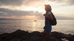 Silhouette du touriste féminin avec le sac à dos et le chapeau admirant le paysage marin stupéfiant au coucher du soleil banque de vidéos