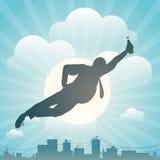 Silhouette du vol d'homme au-dessus de la ville Photos libres de droits