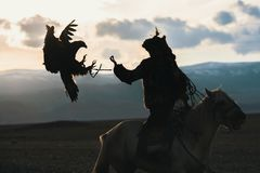 Silhouette of the Eagle Hunter traditional clothing, while hunting with a golden eagle. In desert mountain of Western Mongolia Stock Images