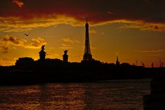 Silhouette of Eiffel Tower and Pont Alexandre III bridge on a colourful evening sky stock photo
