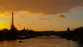 Silhouette of Eiffel Tower and Pont Alexandre III bridge on a warm orange evening sky stock photo