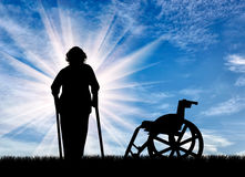 Silhouette of an elderly woman with crutches on background of wheelchair outdoors. Concept of disability and old age Stock Image
