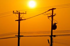 Silhouette of electric pole power lines and wires in sunset Royalty Free Stock Image