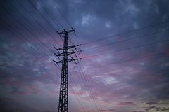 An Electric Pole at Sunset. A silhouette of an electric pole at sunset, with pink clouds in the background Royalty Free Stock Photos