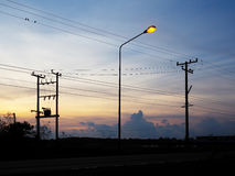Silhouette of electric poles  and cables over sunrise sky background. Stock Photography
