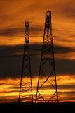 Silhouette of electric pylons. With African sunset in background Stock Photos