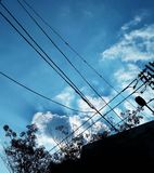 Silhouette of electric wire with clouds. Silhouette of electric wire and building with clouds on blue sky stock image