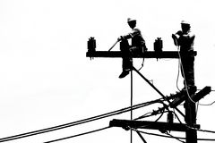 Silhouette electrician working on electricity post Stock Image