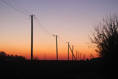 The silhouette of electricity pole at twilight Stock Image