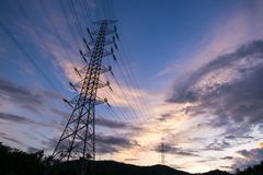 Electricity pylon. A silhouette electricity pylon and line pass through mountains, taken at the sunset royalty free stock photo