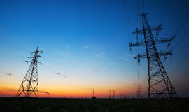 Silhouette of electricity pylons and high-voltage power Royalty Free Stock Images